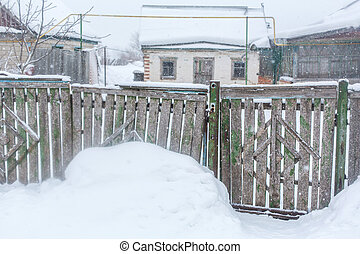 Winter in the village. Old dilapidated rickety fence of wooden boards. A lot of snow around