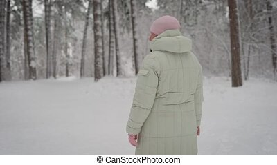 Winter in the wood. The old woman walks in the  on a footpath in the afternoon. The pensioner in  warm jacket and  pink cap spends  free time walking. The  breathes fresh air.