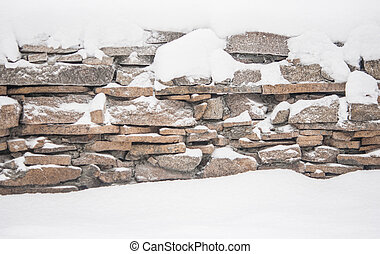 winter in village, stone fence covered by snow