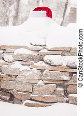 winter in village, stone fence covered by snow with Santa hat