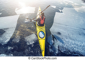 winter kayaking in ukraine - man kayak is on a frozen river