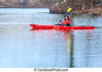 Winter kayaking - Woman is kayaking on a lake under heavy ...