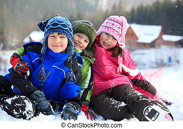 Three Caucasian kids dressed in winter clothes enjoying the snow.