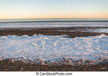 Winter landscape in beach, coastline with cracked ice and opened sea water