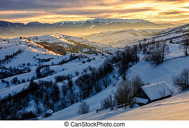 winter landscape in mountainous rural area at sunrise -...