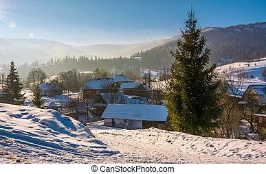 winter landscape in mountainous rural area - village in...