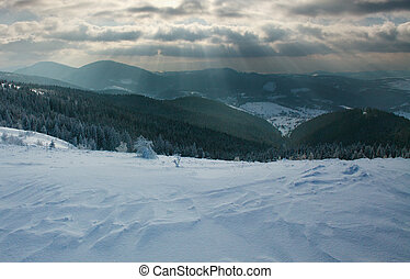 Winter landscape in mountains forest on background of dramatic sky
