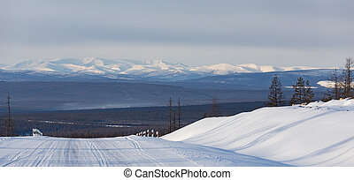 Winter landscape with road and mountains Stanovoi range in South Yakutia, Russia