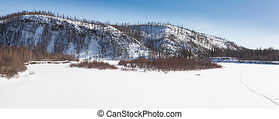 The bed of the frozen river against the backdrop of forested hills