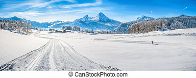 Panoramic view of beautiful winter wonderland landscape in the Bavarian Alps with cross-country slopes and famous Watzmann massif in the background, Nationalpark Berchtesgadener Land, Bavaria, Germany