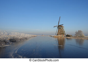 Winter landscape in the Netherlands with windmill and ice