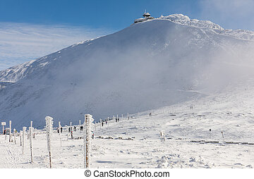 Winter landscape of Krkonose Mountains with Snezka Hill. The valley of a giant mine filled with fog. Beautiful winter landscape Krkonos on a sunny day.