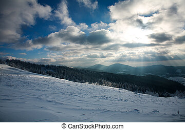 Winter landscape of mountains in rays of the setting sun