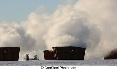 Winter landscape of smoke from chimneys of plant against blue sky frosty misty day