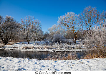 winter landscape of snow-covered trees and river in winter season, Germany