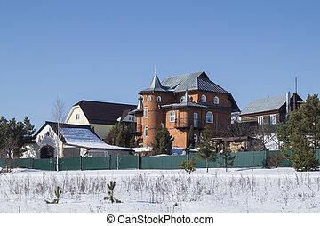 Winter landscape of the cottages on background blue sky