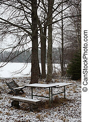 Winter landscape on a lake with tables and chairs