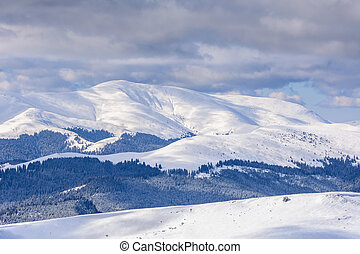 Winter landscape over Carpathian Mountains. Panorama of snow mountain range landscape with blue sky and white clouds from Carpathian Mountains.