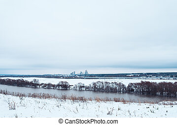 Winter landscape, river against a forest of snow-covered trees. Beautiful winter background in nature. White hills the distance.