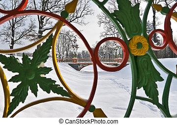 Winter landscape in the park through bridge fence