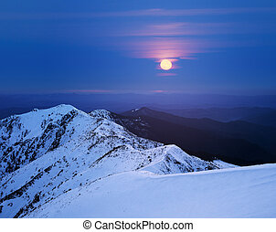 Winter landscape with a full moon in the mountains