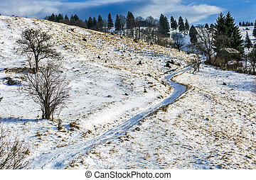 Winter landscape with a snowy countryside road in the mountains