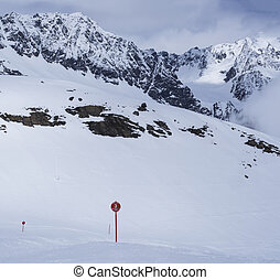 Winter landscape with empty red piste sign, snow covered mountain slopes, spring sunny day at ski resort Stubai Gletscher, Stubaital, Tyrol, Austrian Alps.