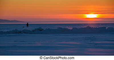 fisherman on the ice of the river at sunset