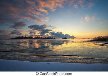 Winter landscape with frozen lake and sunset sky. Colorful orange sky. Composition of nature.