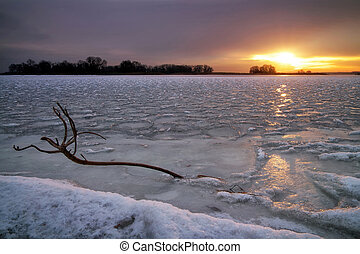 Winter landscape with frozen lake, snag and sunset sky