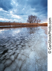 Winter landscape with lake and cloudy sky. Composition of nature.