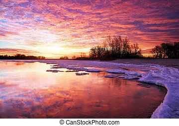 Winter landscape with lake and sunset fiery sky. Composition of