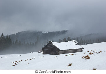 Winter landscape with old house in the mountains