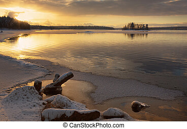 Winter landscape with river and driftwood in the foreground at sunset
