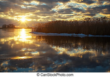 Winter landscape with river, reeds and cloudy sunset sky. Composition of nature.