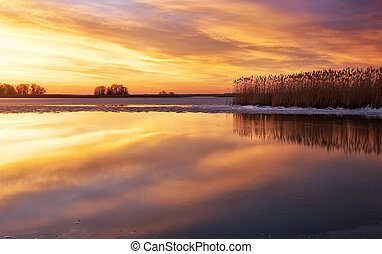 Winter landscape with river, reeds and sunset sky. Beautiful...