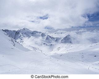 Winter landscape with snow covered mountain slopes and empty pistes, spring sunny day at ski resort Stubai Gletscher, Stubaital, Tyrol, Austrian Alps.