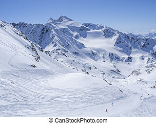 Winter landscape with snow covered mountain slopes and pistes with skiers enjoying spring sunny day at ski resort Stubai Gletscher, Stubaital, Tyrol, Austrian Alps