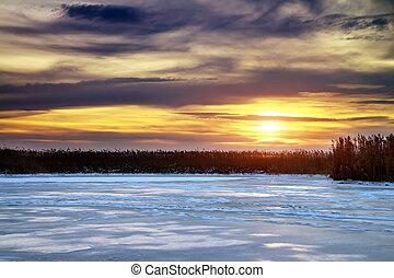 Winter landscape with sun and frozen river. Sunrise.