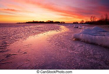 Winter landscape with sunset fiery sky.