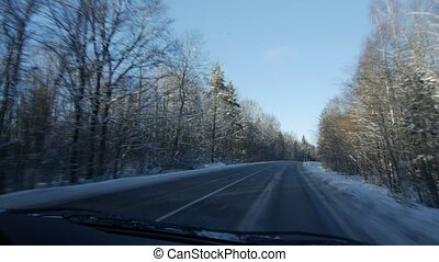 Winter landscape with the road the forest and the blue sky,...