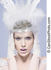 Fine art cool toned portrait of a gorgeous winter maiden wearing a feathery white headdress with her hands in lacy gloves held to her head, closeup head and shoulders