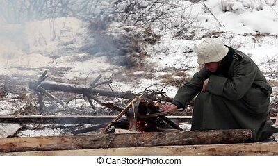Winter military - Soldiers basking campfire in winter close...