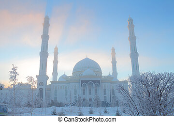 Winter mosque on the background of blue sky