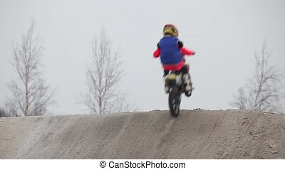 Winter motocross race jumps on motorcycle back view with...