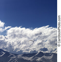 Winter mountain in evening and sunlight silhouette of parachutist