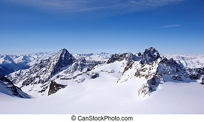 winter mountain landscape in the Swiss Alps with large glaciers and jagged mountain peaks