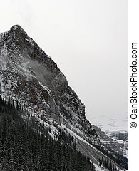 Mountain peak in winter with clouds behind. Lake Louise, Banff National Park, Alberta, Canada.