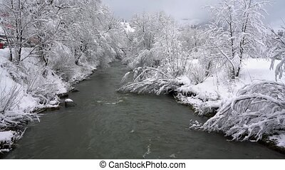 Winter mountain river surrounded by trees and banks of snow-covered