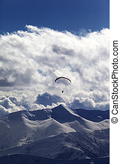 Winter mountains in evening and silhouette of paraglider